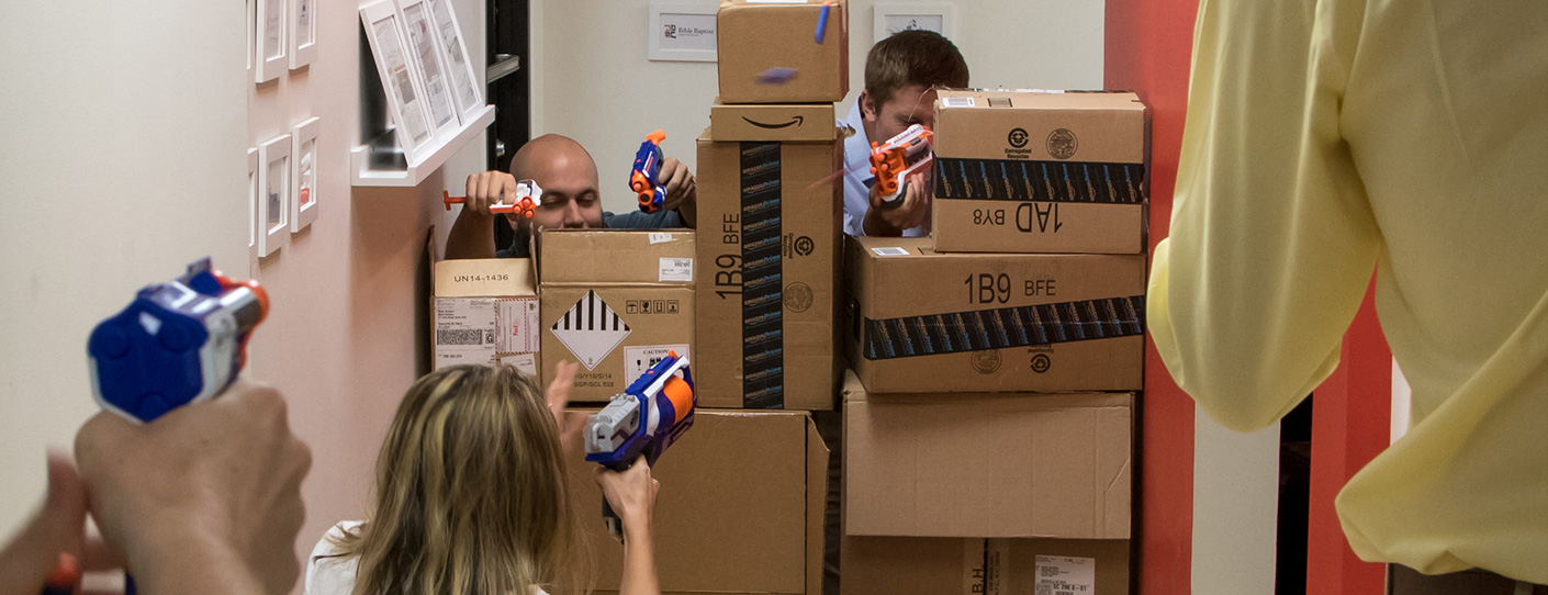Employees engaging in a nerf gun battle